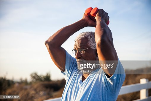 Senior Black Man Exercising Outdoors with Dumbells