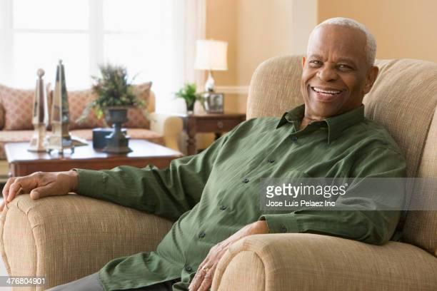 Senior Black man smiling in armchair