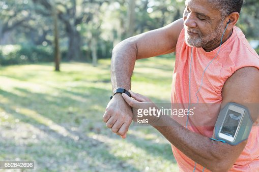 Senior black man with headphones and fitness tracker : Stock-Foto