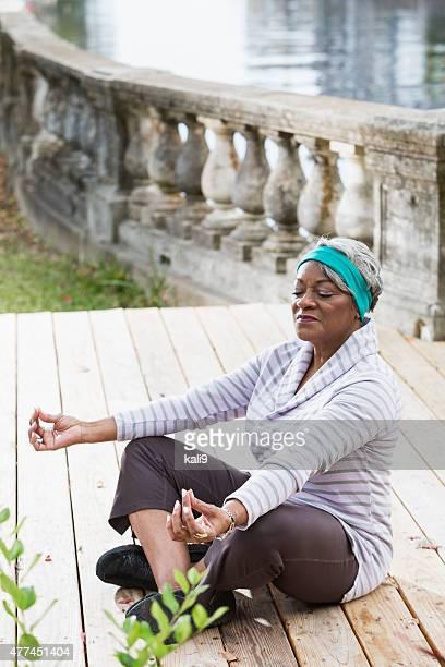 Senior black woman in yoga lotus pose