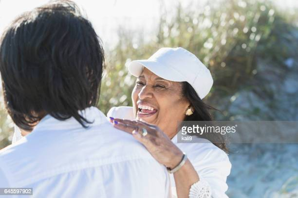 Senior black woman laughing with adult daughter