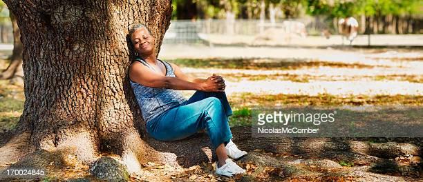 Senior black woman relaxing by large tree enjoying the sun