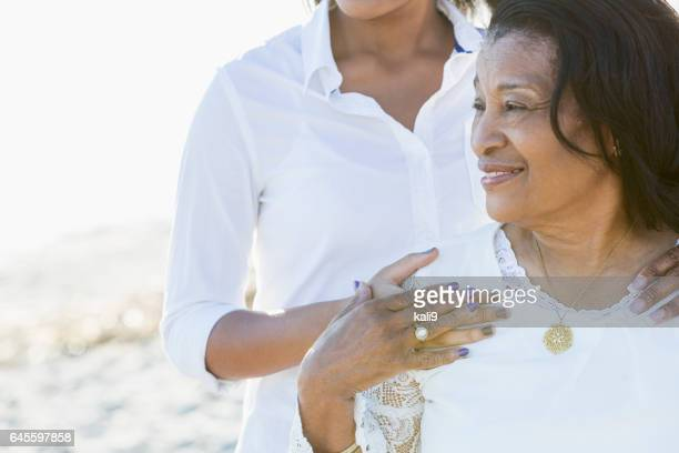 Senior black woman smiling outdoors, with granddaughter