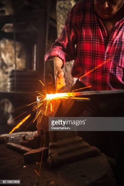 Homme Senior forgeron forge un métier de fer sur l'enclume