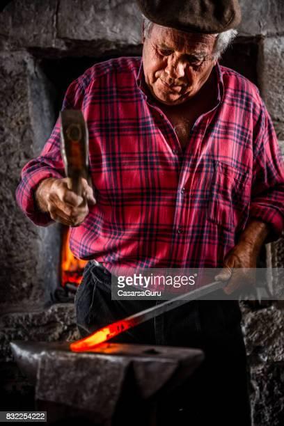 Senior Blacksmith Man Forging Iron Craft on Anvil