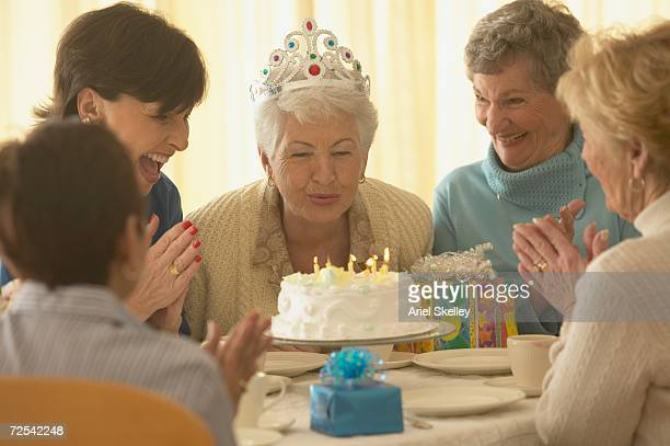Senior blowing out candles on birthday cake