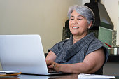 Senior Brazilian woman using laptop together at home