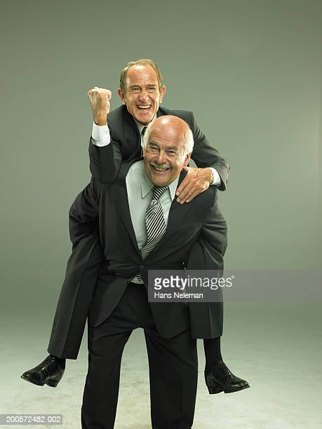 Senior business man giving colleague piggy back, portrait