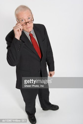 Senior business man looking over glasses, portrait