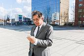 Senior business man on the street text messaging