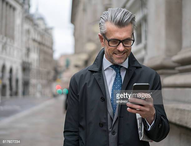 Senior business man texting on his smart phone