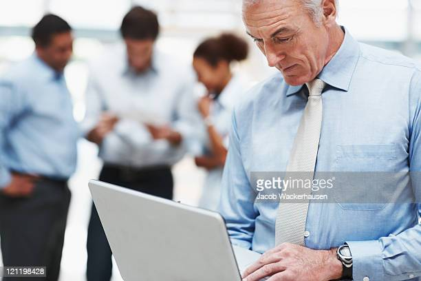 Senior business man using laptop with coworkers at the back