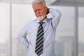 Senior business man with back pain in an office