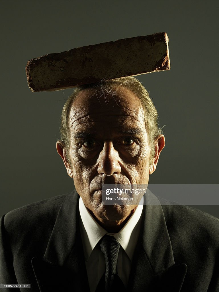 Senior business man with brick on head, portrait : Stock Photo