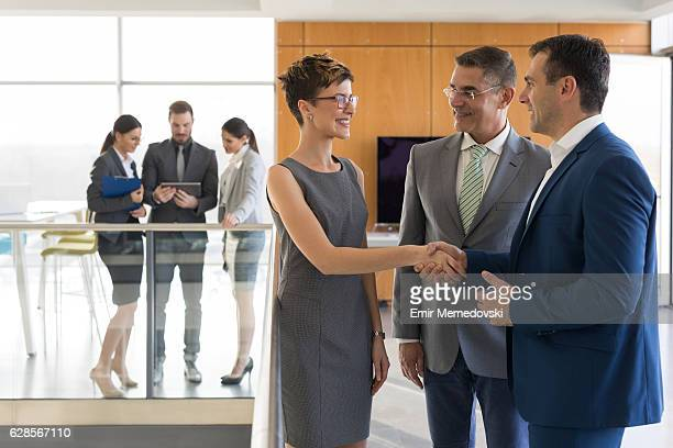 Senior business partner and young female colleague shaking hands