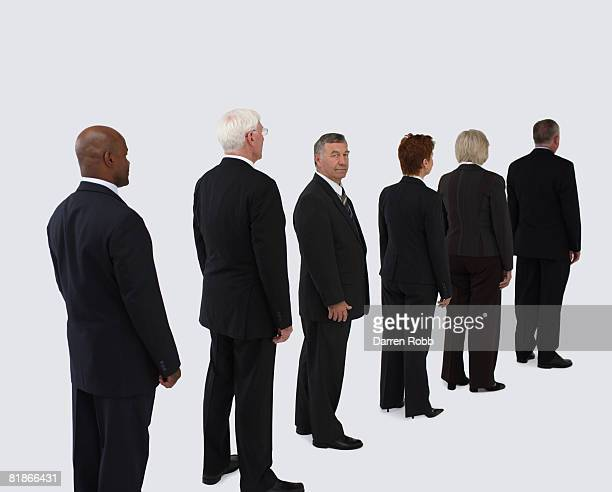 Senior business people standing in a line with one man turning around