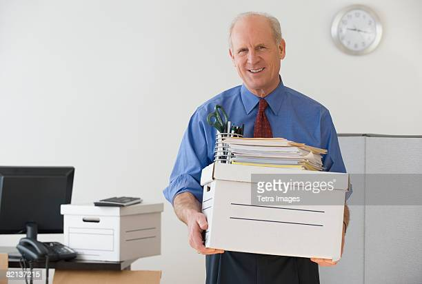 Senior businessman carrying box and office supplies