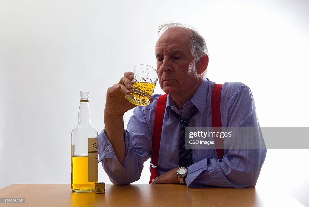 Senior businessman drinking whisky : Stock Photo