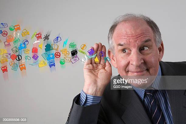 Senior businessman, hand cupped to ear, smiling, close-up with symbols