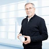 Blue-eyed senior businessman having a break. XXXL size, square composition.