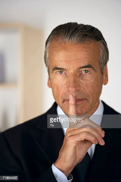Senior businessman holding a finger in front of his mouth