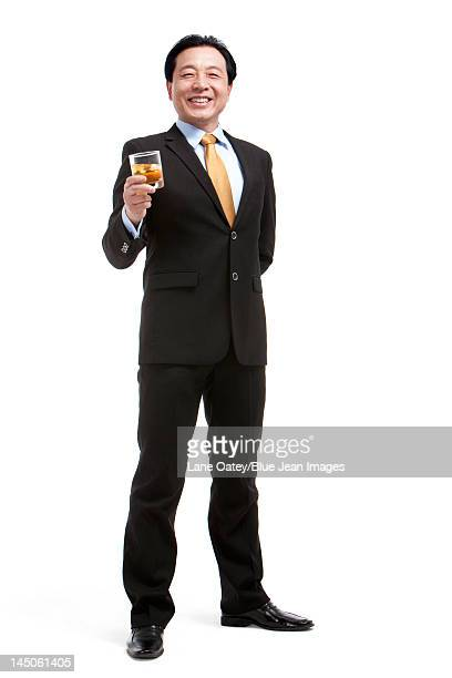 Senior businessman holding a glass of whiskey