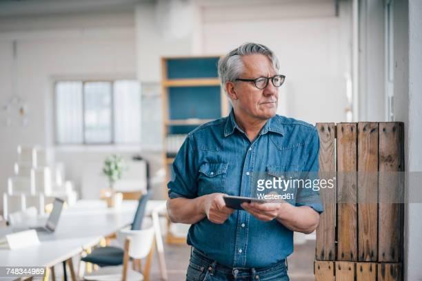 Senior businessman holding tablet in office