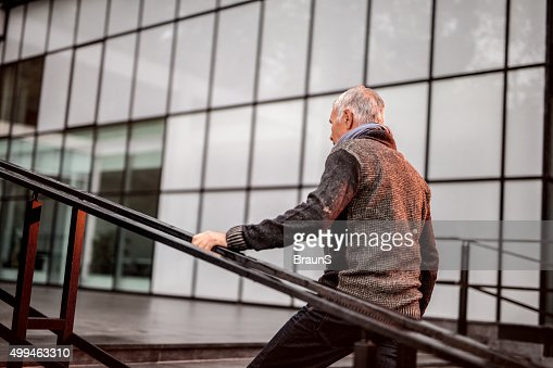 Senior businessman in casual clothing moving up the stairs.