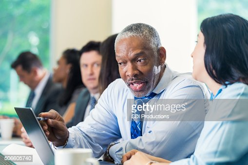 Senior businessman in meeting or conference with professional colleagues