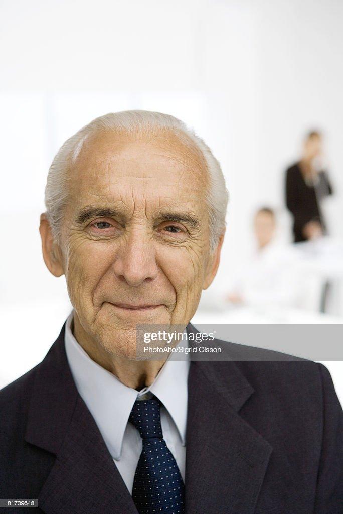 Senior businessman in office, smiling, portrait