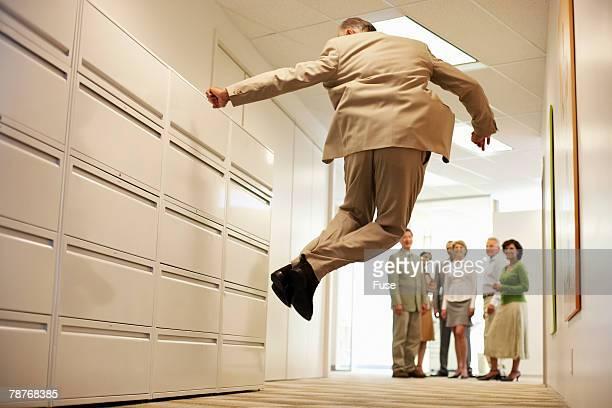 Senior Businessman Jumping in Corridor