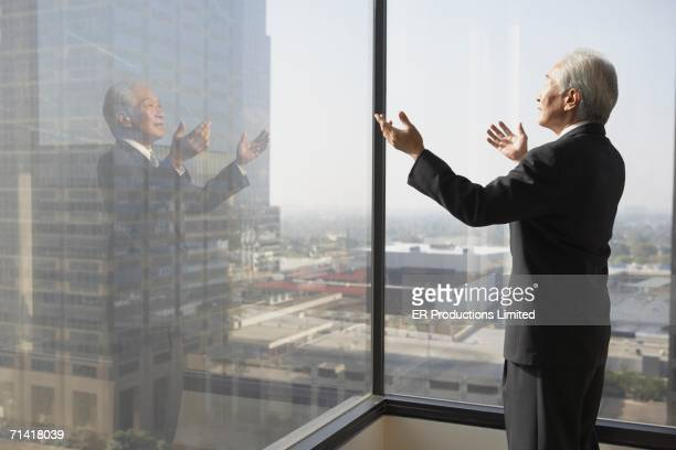 Senior businessman looking out a window