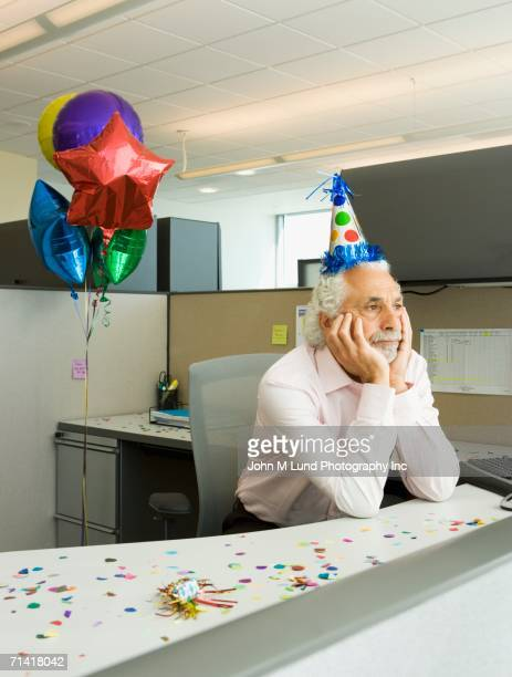 Senior businessman looking sad in a cubicle with a party hat and a bunch of balloons