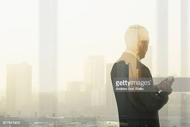 Senior businessman overlooks city from office