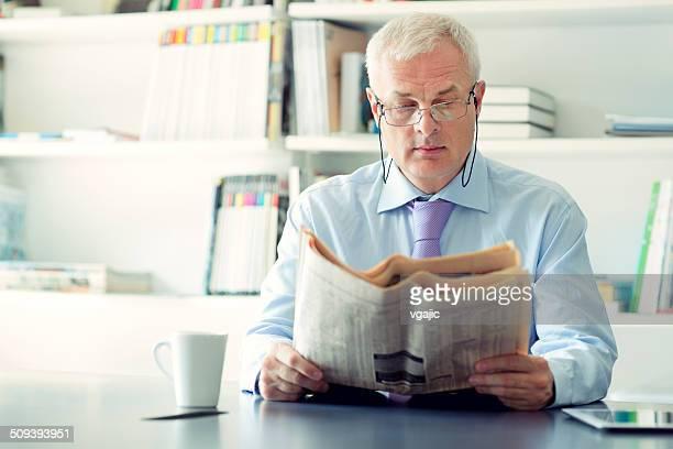 Senior businessman reading newspaper in office.