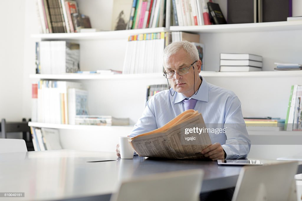 Senior businessman reading newspaper in office.