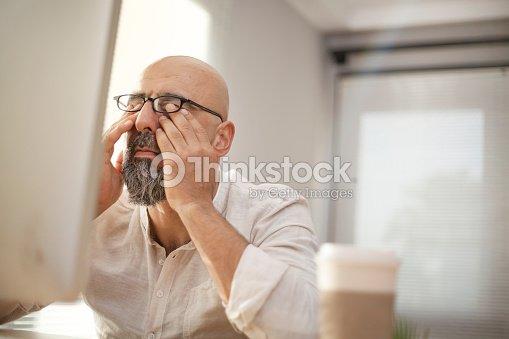 Senior businessman rubbing his tired eyes : Stock Photo