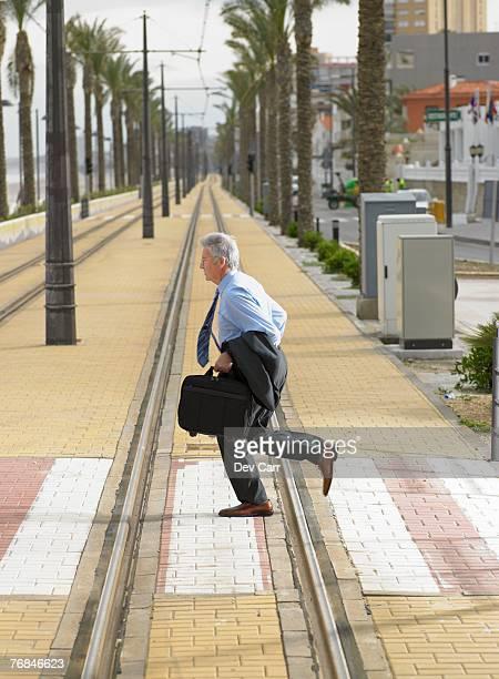 Senior businessman running across pedestrian crossing on tramway