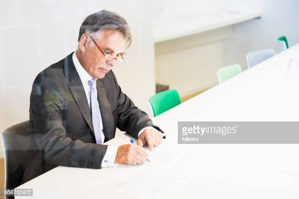 Senior businessman signing documents in modern conference room