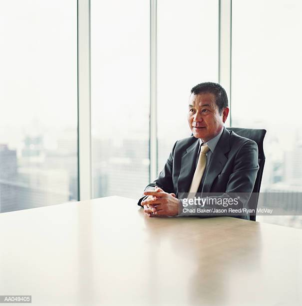 Senior businessman sitting at conference table