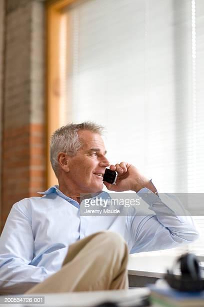 Senior businessman sitting at desk using mobile phone, smiling