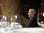 Senior businessman sitting at table in restaurant, view across table