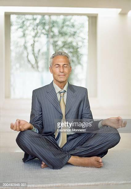 Senior businessman sitting in lotus yoga position