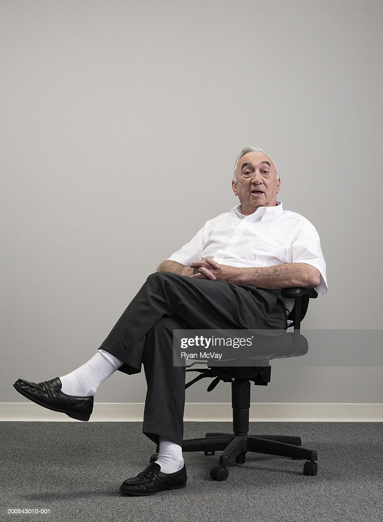 Senior businessman sitting on office chair, portrait : Stock Photo