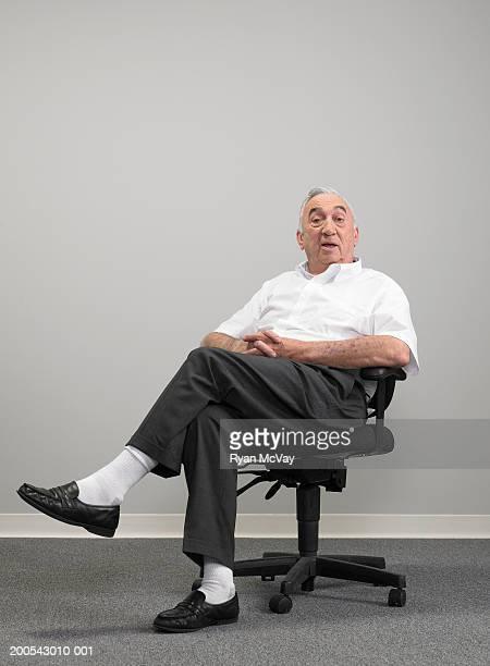 Senior businessman sitting on office chair, portrait