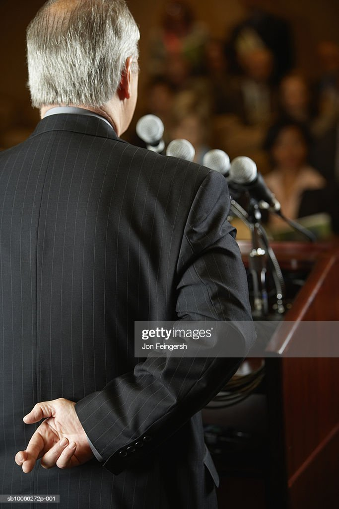 Senior businessman speaking into microphone, rear view