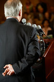 Senior businessman speaking into microphone, rear view