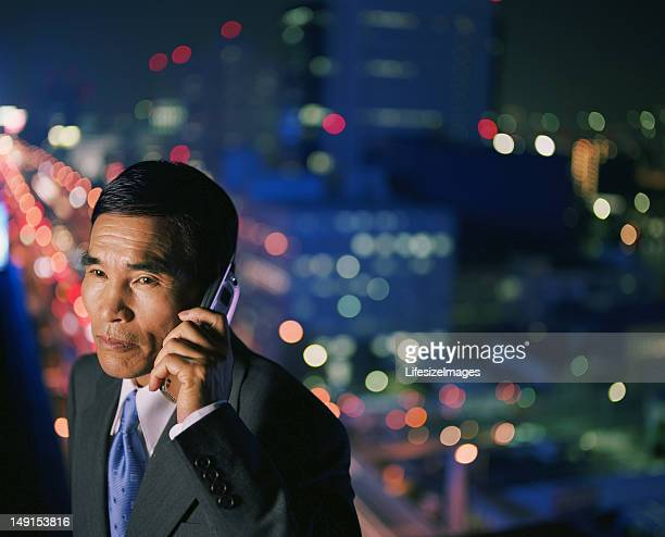 シニアビジネスマンが携帯電話で話している、交通の背景、