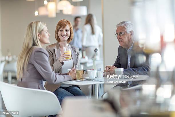 Senior businessman talking to team at breakfast table in hotel restaurant