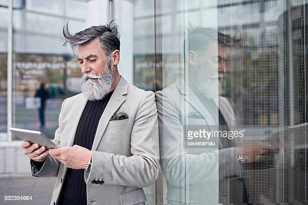 Senior businessman using digital tablet in office building